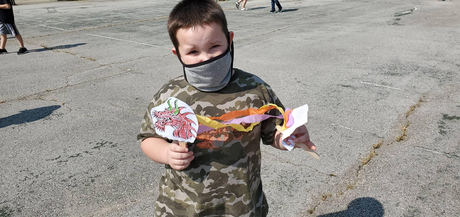 Student holding dragon craft.